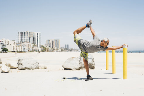Senior man, exercising on beach, stretching leg, Long Beach, California, USA - ISF09323