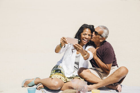Senior couple sitting on beach, taking selfie with smartphone, Long Beach, California, USA - ISF09329