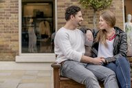 Romantic young couple sitting on bench, Kings Road, London, UK - CUF23144