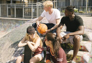Male and female basketball friends chatting in city skatepark - CUF23153