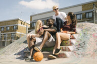 Four male and female basketball friends sitting chatting in city skatepark - CUF23159