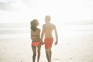Rear view of young couple in swimwear strolling on sunlit beach, Cape Town, Western Cape, South Africa - CUF23198