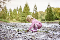 Baby girl wearing rubber boots playing in muddy puddle - CUF23216
