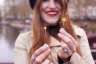 Portrait of woman holding mini sparklers - CUF23276