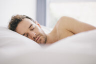 Young man lying on side asleep in bed - CUF23321