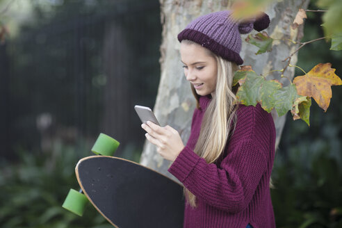 Smiling teenage girl looking at cell phone holding skateboard - ZEF15595