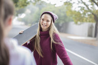 Smiling teenage girl holding skateboard meeting with friend - ZEF15601