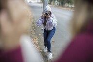 Teenage girl taking a picture of her friends on the street - ZEF15604