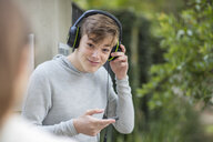 Boy listening to music from headphones - ZEF15610