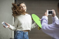 Friend taking picture of carefree teenage girl dancing while holding skateboard and listening to music - ZEF15613