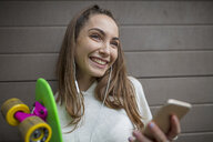 Portrait of smiling teenage girl with cell phone, earphones and skateboard - ZEF15616