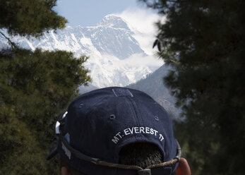 Nepal, Solo Khumbu, Everest, Sagamartha National Park, Man looking at view, wearing cap with Mt. Everest writing - ALRF01248