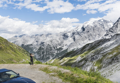 Rear view of woman photographing mountain, Passo di Stelvio, Stelvio, Italy - CUF23371