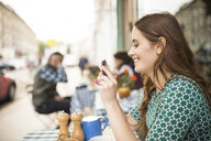 Side view of woman at pavement cafe looking at smartphone smiling - CUF23398
