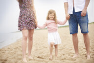 Family holding hands walking on beach - CUF23416