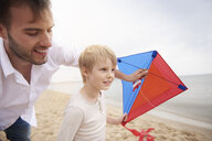 Father and son playing kite on beach - CUF23419
