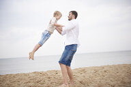 Father swinging son on beach - CUF23434