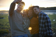Four young adults taking smartphone selfie at seaside sunset - CUF23443