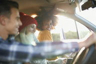 Three young adult friends in sunlit car - CUF23449