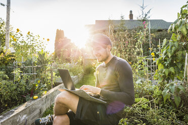 Man typing on laptop in sunlit community garden, Vancouver, Canada - CUF23452
