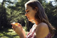 Young woman gazing at yellow crystal in forest, Sattelbergalm, Tyrol, Austria - CUF23464