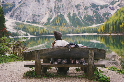 Woman relaxing on park bench, Lago di Braies, Dolomite Alps, Val di Braies, South Tyrol, Italy - CUF23566