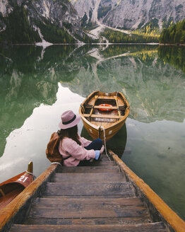 Woman relaxing on pier, Lago di Braies, Dolomite Alps, Val di Braies, South Tyrol, Italy - CUF23569