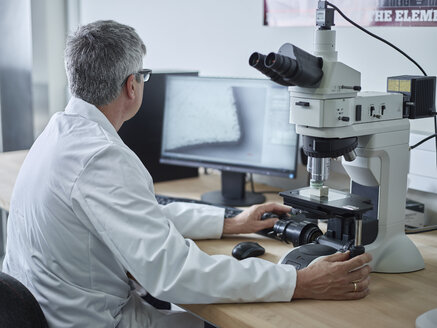 Physician working with microscope, looking on screen - CVF00720