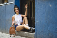 Portrait of fashionable woman wwith small backpack waiting in front of house entrance - JSMF00298