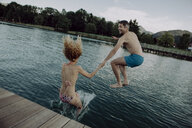 Happy couple jumping hand in hand into swimming lake - JLOF00044