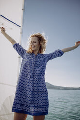 Happy woman standing on a sailing boat - JLOF00053