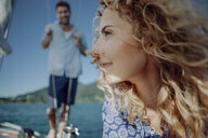 Smiling woman on a sailing boat with man in background - JLOF00065