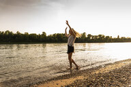 Young woman walking barefoot on riverside in the evening - UUF14032