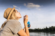 Blond woman blowing soap bubbles - UUF14038
