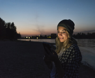 Young woman using smartphone on riverside in the evening - UUF14074