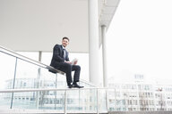 Suited young businessman sitting on office railings using digital tablet - CUF23634