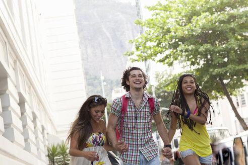 Three adult friends running and holding hands on street, Copacabana town, Rio De Janeiro, Brazil - CUF23681