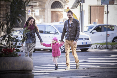 Couple and daughter holding hands on pelican crossing, Cagliari, Sardinia, Italy - CUF23696