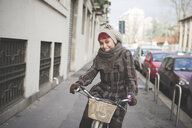 Portrait of young woman riding bicycle, wearing winter clothes - CUF23732