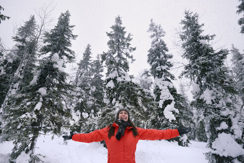 Young woman celebrating in snow covered forest, Posio, Lapland, Finland - CUF23735