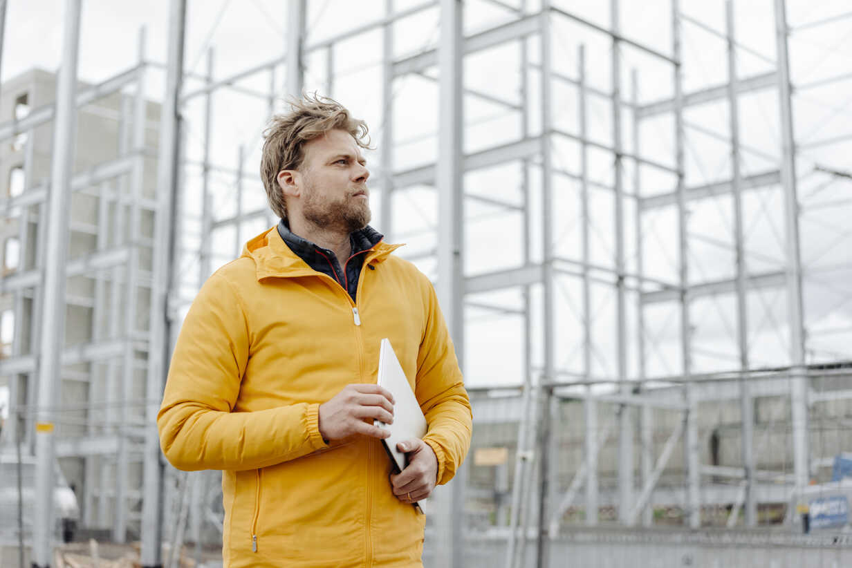 Man holding laptop, construction site in the background - KNSF03979 - Kniel Synnatzschke/Westend61