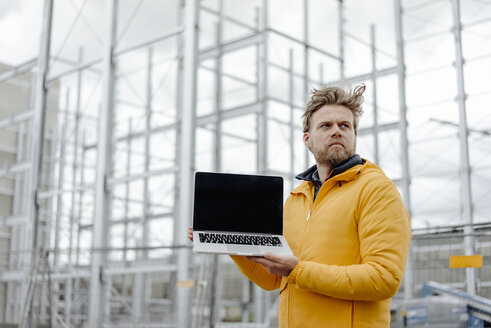 Man holding laptop, construction site in the background - KNSF03982