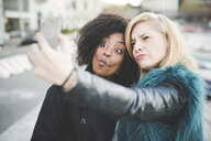 Two young women pulling faces for smartphone selfie, Lake Como, Como, Italy - CUF23748