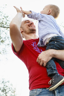 Father holding son, son giving father a high five, low angle view - CUF23835