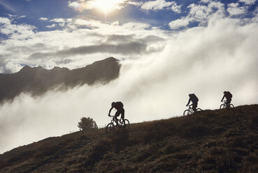 Three people mountain biking, Valais, Switzerland - CUF23886