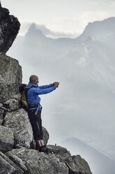Mature man on rocks taking photo, Valais, Switzerland - CUF23892