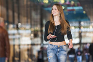 Young woman listening to smartphone music whilst strolling in shopping mall - CUF23949