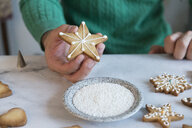 Man's hand holding Christmas Cookie, close-up - SKCF00486
