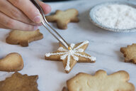 Man's hand decorating Christmas cookie, close-up - SKCF00489