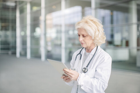 Female doctor standing outside building, using digital tablet - CUF23997